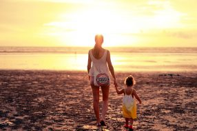 Mum and child walking on beach photo