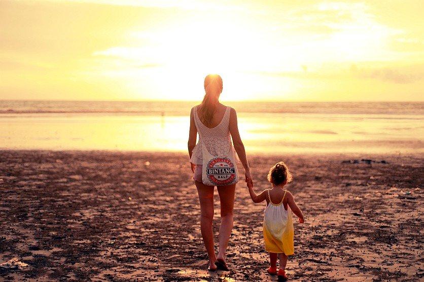 Mum and child walking on beach photo